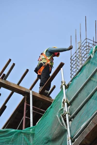 Bauarbeiter steht auf wackligen Brettern auf Baustelle in großer Höhe und blickt nach unten
