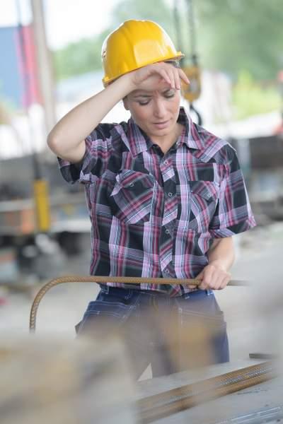 Eine kranke Angestellte mit gelbem Schutzhelm wischt sich den Schweiß ab und versucht sich zu konzentrieren