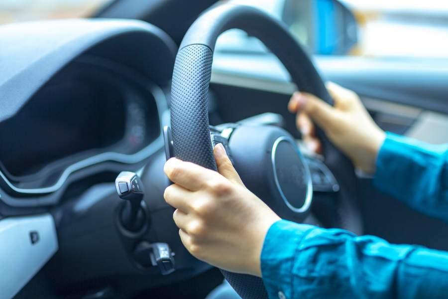 Hände umklammern das Lenkrad eines Autos für sicheres Fahren