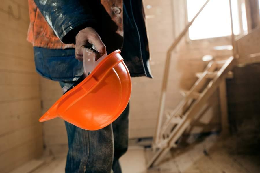 Handwerker hält einen neuen orange-farbenen Schutzhelm in der Hand auf der Baustelle