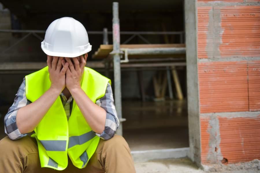 Frustrierter müder Arbeiter mit weißem Schutzhelm und Warnweste schlägt die Hände vor das Gesicht