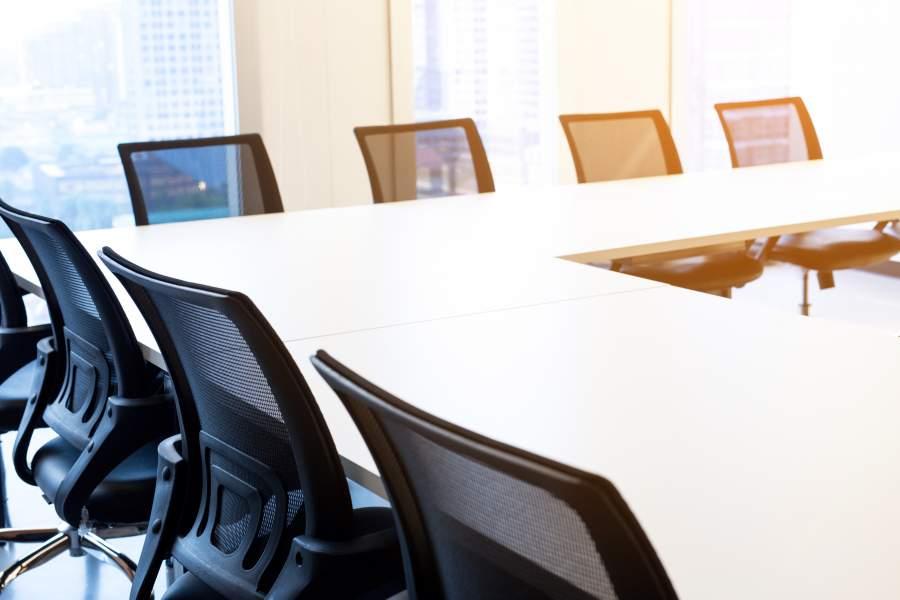 Leere bequeme Stühle mit schwarzer Rücklehne an weißen Tischen über Eck in Workshop-Formation für offene Diskussionsrunden