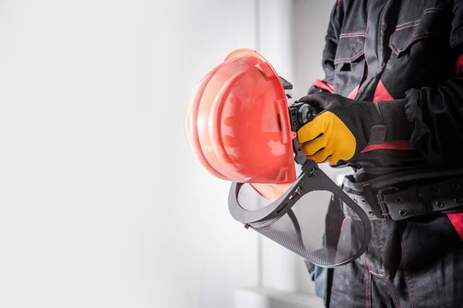 Mitarbeiter in Arbeitskleidung und Sicherheitshandschuhen hält orange-farbenen Schutzhelm mit Gesichtsvisier in Händen
