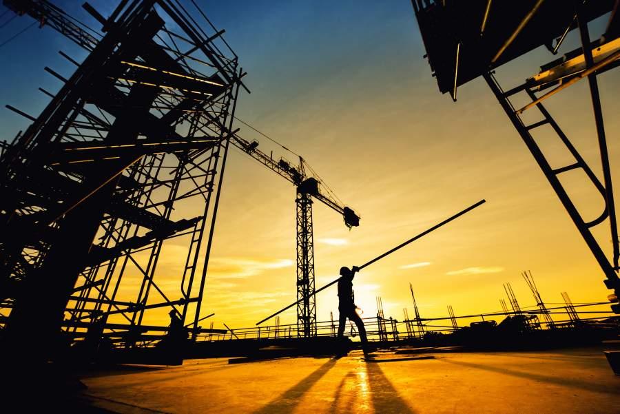 Silhouette eines Mitarbeiters, der eine lange Eisenstange über der Schulter über die Baustelle trägt, mit Sonnenuntergang im Hintergrund