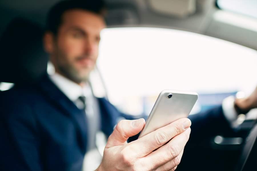 Mann im Anzug sitzt am Lenkrad des Autos und schaut auf sein Smartphone in der Hand und lässt sich absichtlich ablenken