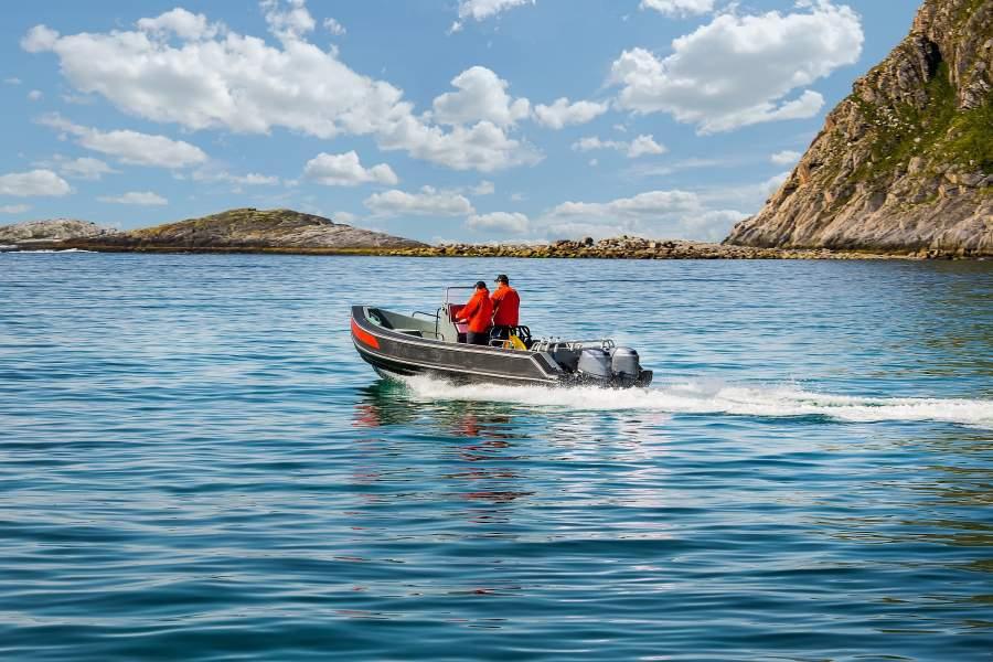 Zwei Männer fahren auf einem kleinen Motorboot aus der Bucht